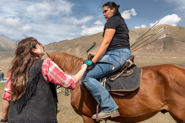 Serena Caballero receives support from her teammate Susannah Winfield before competing in the final rounds of mounted archery, where she will place third. Despite the competitive nature of these sports, the women are very supportive to one another; many say the best thing about competing is meeting people from all over the world, learning about other cultures, and new friends. (Photo by Eleanor Moseman/The Guardian)