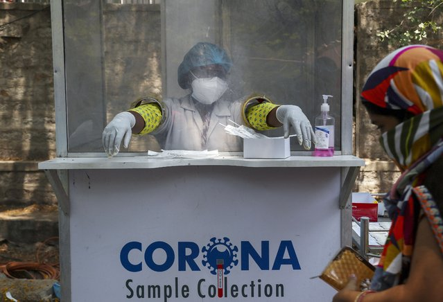 An Indian health worker takes a break between collecting swab samples for COVID-19 test in Hyderabad, India, Monday, May 3, 2021. (Photo by Mahesh Kumar A./AP Photo)