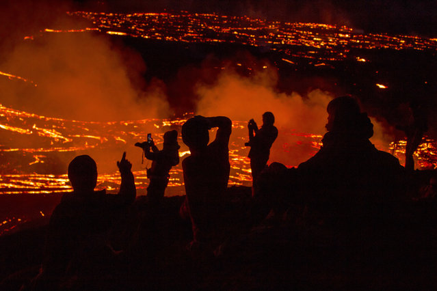 People watch as lava flows from an eruption of a volcano on the Reykjanes Peninsula in southwestern Iceland late on Monday, March 29, 2021. Iceland's latest volcano eruption is still attracting crowds of people hoping to get close to the gentle lava flows. The eruption in Geldingadalur, near Iceland's capital Reykjavik, is not seen as a threat to nearby towns and the slow flows mean people can get close to action without too much harm. (Photo by Marco Di Marco/AP Photo)