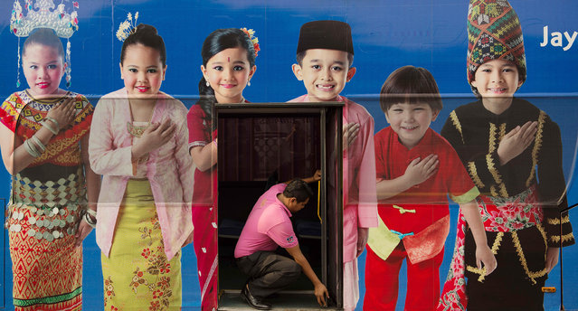 """A man (C) opens a bus door through within a poster showing the Malaysia ethnic communities with traditional dress in Kuala Lumpur on September 25, 2013. The Malaysian government's new measures to benefit the Malay majority are angering the multi-ethnic nation's other races and raising fears they could accelerate a """"brain drain"""" of talent heading overseas. (Photo by Mohd Rasfan/AFP Photo)"""