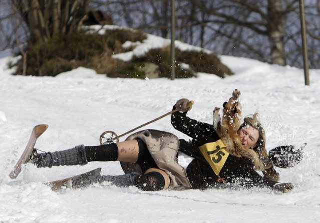 A participant falls on vintage skis during a traditional historical ski race in the northern Bohemian town of Smrzovka February 21, 2015. (Photo by David W. Cerny/Reuters)
