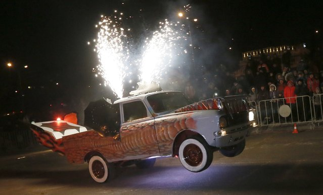 "A member of the ""Winged"" motor theatre performs while driving a customized ""Moskvich"" Soviet made car during the annual ""Winter Virage"" motor sports festival dedicated to the Defender of the Fatherland Day on an embankment of the Yenisei River in Russia's Siberian city of Krasnoyarsk, February 23, 2015. (Photo by Ilya Naymushin/Reuters)"