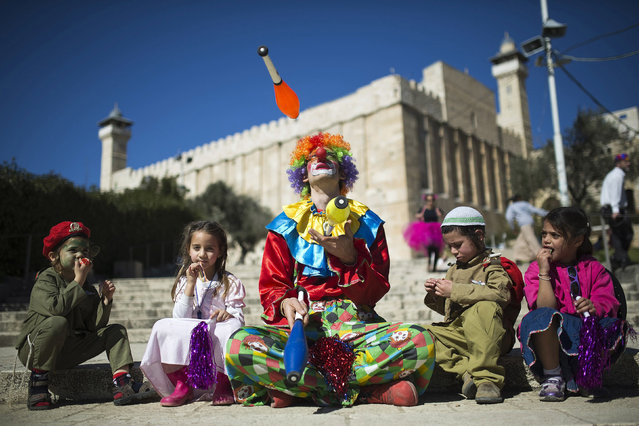 A Jewish settler dressed as a clown juggles next to children as the Tomb of the Patriarchs is seen in the background, during a parade marking the Jewish holiday of Purim in the West Bank city of Hebron March 5, 2015. Purim is a celebration of the Jews' salvation from genocide in ancient Persia, as recounted in the Book of Esther. REUTERS/Amir Cohen (WEST BANK - Tags: RELIGION SOCIETY TPX IMAGES OF THE DAY)