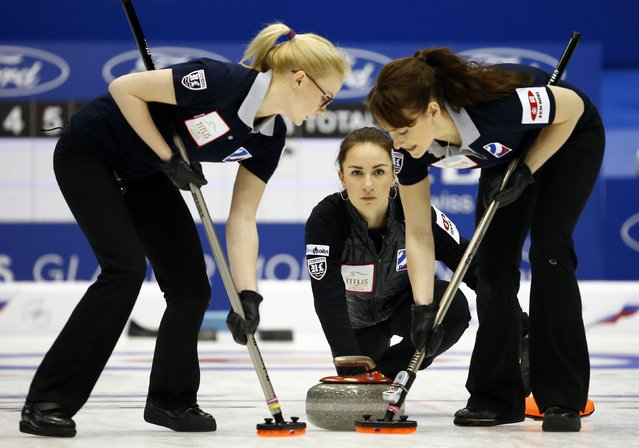 Russia's Anna Sidorova delivers a stone as her teammates Alexandra Saitova and Ekaterina Galkina sweep during their curling round robin game against Sweden at the World Women's Curling Championships in Sapporo March 16, 2015. (Photo by Thomas Peter/Reuters)