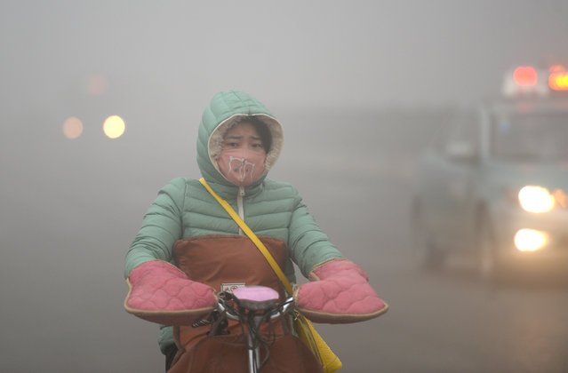A citizen rides in smog on December 20, 2016 in Jinan, Shandong Province of China. Air quality index (AQI) readings exceeded 400 and some schools have suspended classes in Jinan. (Photo by VCG/VCG via Getty Images)