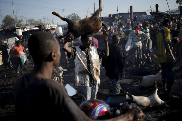 A butcher carries a butchered goat on his head at La Saline slaughterhouse in Port-au-Prince, Haiti, April 4, 2015. (Photo by Andres Martinez Casares/Reuters)