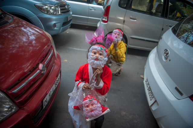 A boy and a girl pose with Santa masks while selling them on traffic lights on December 23, 2016 in New Delhi, India. Christmas spells a different business across traffic signals in many parts of India. In the capital itself, a common sight leading up to Christmas are children as young as 6-7 hawking decorations like Santa masks and caps at major traffic intersections. These children work different stop lights and once the light turns green, they regroup to discuss the each round's profits or losses. (Photo by Shams Qari/Barcroft Images)
