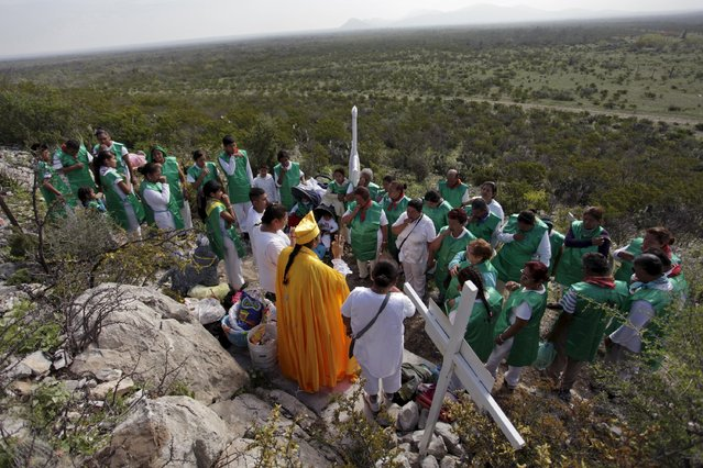 A medium or materia (C) prays to penitents at the Cerro de la Campana (or hill of the bell) during celebrations for El Nino Fidencio in the town of Espinazo, on the outskirts of Monterrey March 19, 2015. (Photo by Daniel Becerril/Reuters)
