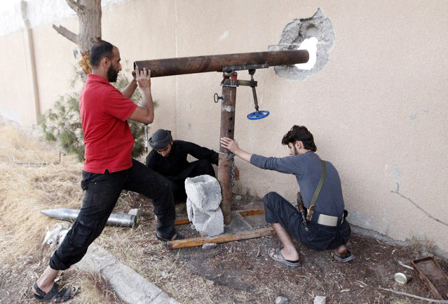 Free Syrian Army fighters prepare to fire rockets towards forces loyal to Syria's president Bashar al-Assad  in Raqqa, eastern Syria October 14, 2013. (Photo by Nour Fourat/Reuters)