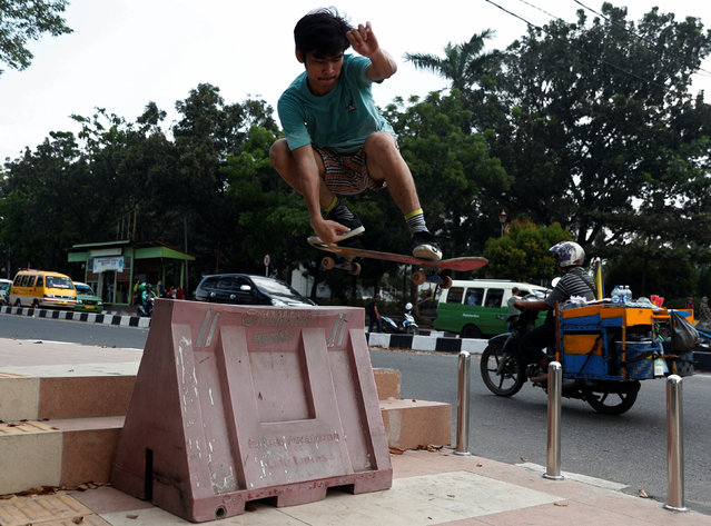 A youth skates next to a road in Palembang, South Sumatra, Indonesia on August 15, 2018. (Photo by Edgar Su/Reuters)