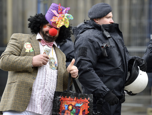 A reveller jokes  next to  a police officer during the start of the street carnival in Cologne, Germany, on Thursday, February 4, 2016. (Photo by Martin Meissner/AP Photo)