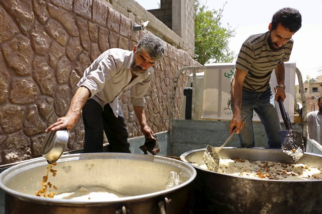 Men serve residents free meals from a soup kitchen in the besieged town of Deir al-Asafir in the Eastern Ghouta of Damascus May 19, 2015. (Photo by Amer Almohibany/Reuters)