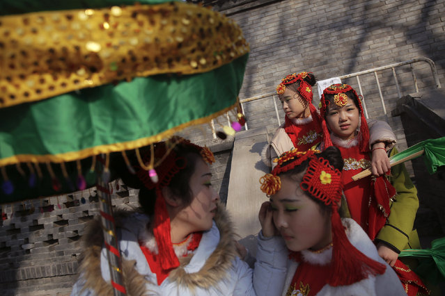 A girl helps the other one with make-up as performers wait for their turn to go onto the stage at the Longtan park as the Chinese Lunar New Year, which welcomes the Year of the Monkey, is celebrated in Beijing, China February 9, 2016. (Photo by Damir Sagolj/Reuters)