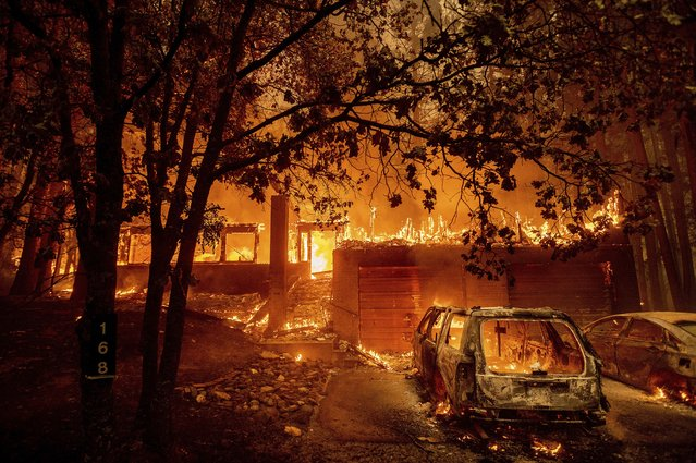 Flames consume a home as the Dixie Fire tears through the Indian Falls community in Plumas County, Calif., Saturday, July 24, 2021. (Photo by Noah Berger/AP Photo)