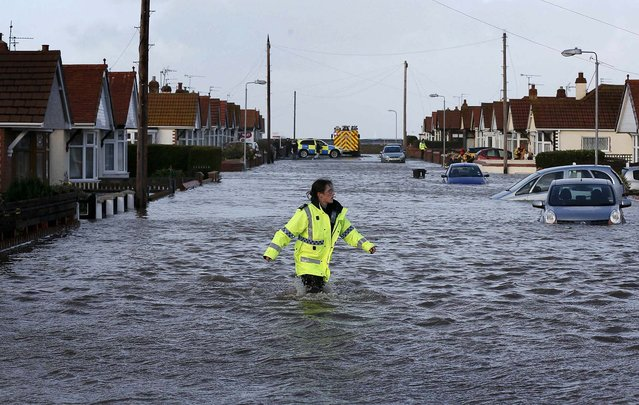 An emergency rescue service worker walks through flood water in a residential street in Rhyl, Wales, on December 5, 2013. Hurricane-force winds disrupted transport and power supplies in Scotland and threatened costal flooding in England as they closed on northern Europe in what meteorologists said could be one of the most powerful storms to hit the continent in years. (Photo by Phil Noble/Reuters)
