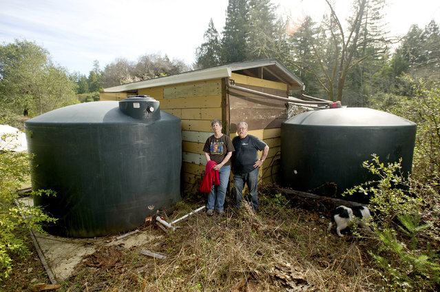 Mark and Ellen Fontaine stand beside water tanks at their home in Philo, February 25, 2014. As drought conditions continue in Northern California, the couple now relies on water deliveries by truck to supply their home. (Photo by Noah Berger/Reuters)