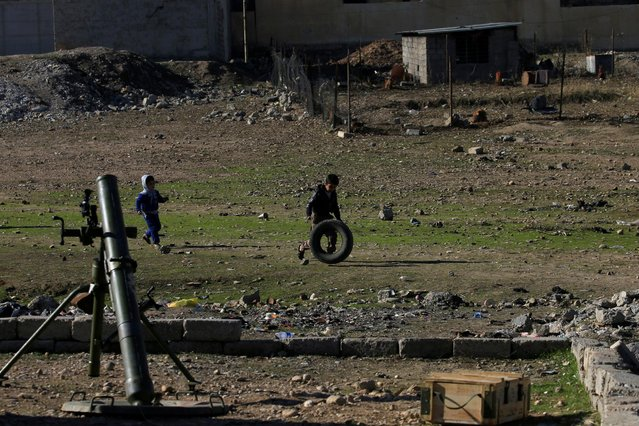 Children play during a battle between Iraqi forces and Islamic State militants in Wahda district of eastern Mosul, Iraq, January 6, 2017. (Photo by Alaa Al-Marjani/Reuters)
