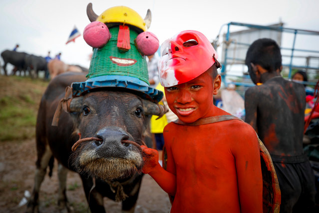 A young Thai boy painted and wearing a costume poses next to a buffalo before the buffalo parade during the annual water buffalo races in Chonburi province, Thailand, 23 October 2018. Around three hundred buffalos take part in the centuries old water buffalo racing festival, divided into categories according to the buffalo's age. The anual festival is held every October among rice farmers to celebrate the rice harvest and mark the end of the Buddhist Lent. (Photo by Diego Azubel/EPA/EFE)