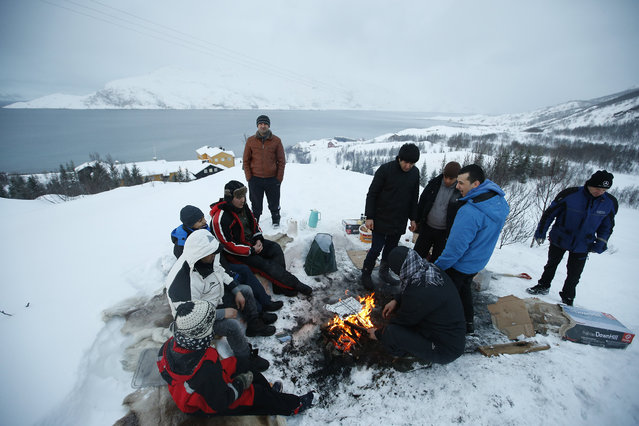 In this photo taken Tuesday, February 2, 2016, asylum seekers gather round a fire as they cook a meal overlooking the temporary Altnes camp refugee camp on the island of Seiland, northern Norway. (Photo by Alastair Grant/AP Photo)