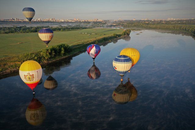 Hot-air balloons float over the Oka River during the Russian Sky International Balloon Festival in Ryazan Region, Russia on July 26, 2021. (Photo by Alexander Ryumin/TASS)