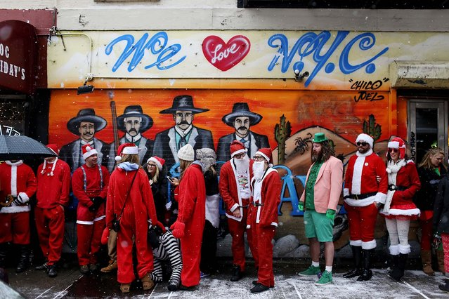 SantaCon 2013 participants line up to get into Doc Holliday's, a bar in the East Village neighborhood of New York (Photo by Kirsten Luce/The New York Times)