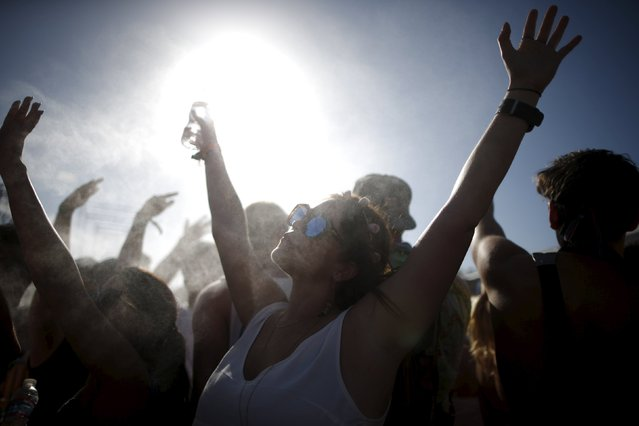 People cool off in misters at the Coachella Valley Music and Arts Festival in Indio, California April 12, 2015. (Photo by Lucy Nicholson/Reuters)