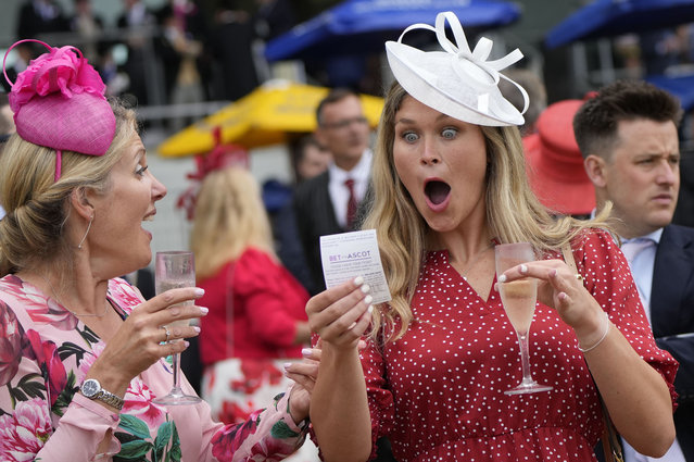 A racegoer reacts to picking a winner in the first race on the third day of the Royal Ascot horserace meeting, which is traditionally known as Ladies Day, at Ascot, England Thursday, June 17, 2021. (Photo by Alastair Grant/AP Photo)
