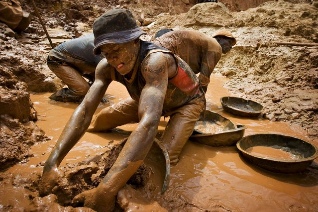 """A gold miner scoops mud while digging an open pit at the Chudja mine in the Kilomoto concession near the village of Kobu in this February 23, 2009 file photo. European importers of minerals from conflict zones should be forced to certify their goods """"blood-free"""", an influential group of EU lawmakers said on April 14, 2015, seeking to toughen a proposal to prevent the financing of warlords in Africa. (Photo by Finbarr O'Reilly/Reuters)"""