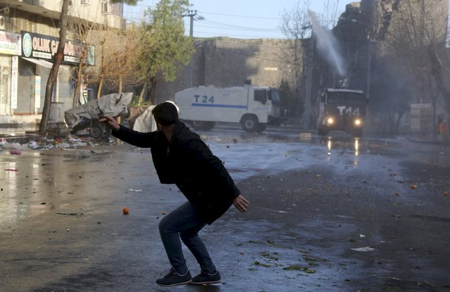 A man runs to take cover as Turkish riot police use a water cannon to disperse Kurdish demonstrators during a protest against a curfew in Sur district and security operations in the region, in the southeastern city of Diyarbakir, Turkey March 2, 2016. (Photo by Sertac Kayar/Reuters)