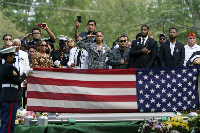 Rosalinda Rosario, center, salutes the casket of her sister, Sgt. Johanny Rosario Pichardo, a U.S. Marine who was among 13 service members killed in a suicide bombing in Afghanistan, during her burial service in Lawrence, Mass., Tuesday, September 14, 2021. (Photo by David Goldman/AP Photo)