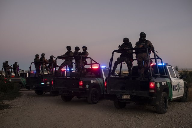 Mexican police stand guard near the Rio Grande river in Ciudad Acuna, Mexico, at dawn Thursday, September 23, 2021, on the border with Del Rio, Texas. Mexico has been ramping up efforts to relieve migrant numbers at this segment of the border. (Photo by Felix Marquez/AP Photo)