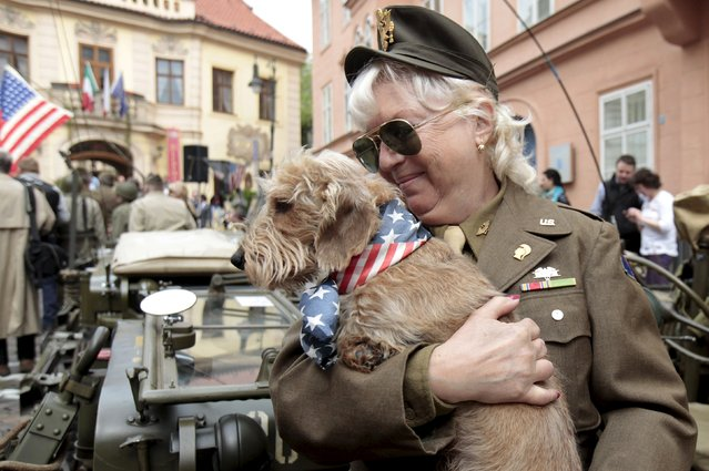 A member of a historical military club in World War Two uniform holds her dog in front of the U.S. embassy in Prague April 24, 2015. The traditional Convoy of Liberty commemorates the 70th anniversary of the liberation of the western part of the country from Nazi rule by the U.S. Army. (Photo by David W. Cerny/Reuters)