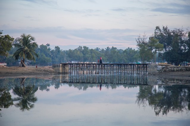 Villagers cross the bridge linking Kutubdia shanty town, in Cox's Bazar, with the dry fish yards, where many of them work. (Photo by Noor Alam/Majority World)