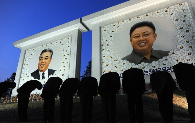 North Koreans pay their respects in front of two portraits, one of founding leader Kim Il-Sung (L) and the other of his son Kim Jong-Il in Pyongyang on April 9, 2012. (Photo by Pedro Ugarte/AFP Photo)