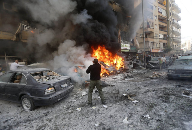 Lebanese men try to extinguish fire from burning cars following an explosion on January 21, 2014 in Haret Hreik, a south Beirut neighbourhood considered a stronghold of the Lebanese Shiite movement Hezbollah. Two people were killed in the apparent suicide car bombing, Lebanon's National News Agency said. (Photo by AFP Photo/STR)