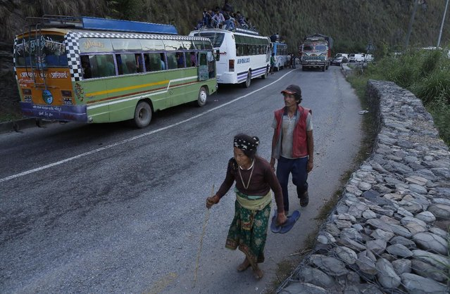 Local residents walk past vehicles held up in a traffic jam on the mountain highway from Kathmandu near the epicenter of Saturday's massive earthquake in the Gorkha District, Nepal, Monday, April 27, 2015. Shelter, fuel, food, medicine, power, news, workers – Nepal's earthquake-hit capital was short on everything Monday as its people searched for lost loved ones. (Photo by Wally Santana/AP Photo)