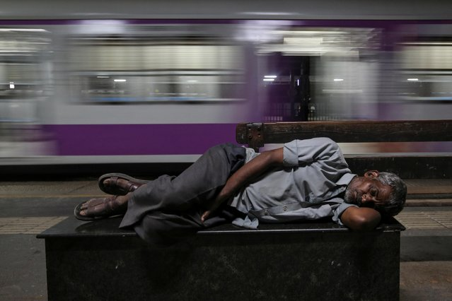 A man sleeps on a bench next to a passing train at a railway station in Mumbai, March 6, 2019. (Photo by Francis Mascarenhas/Reuters)
