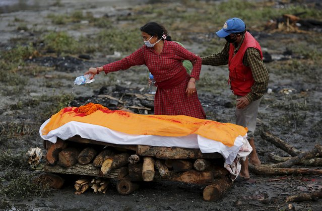 A woman performs the last rites of one of her family member, who died in Saturday's earthquake, during the cremation along a river in Kathmandu, Nepal April 28, 2015. (Photo by Adnan Abidi/Reuters)