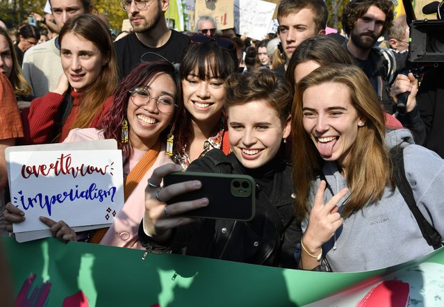 Belgian climate activist Anuna De Wever, center, takes a selfie as she poses with participates in a climate march in Brussels, Sunday, October 10, 2021. (Photo by Geert Vanden Wijngaert/AP Photo)