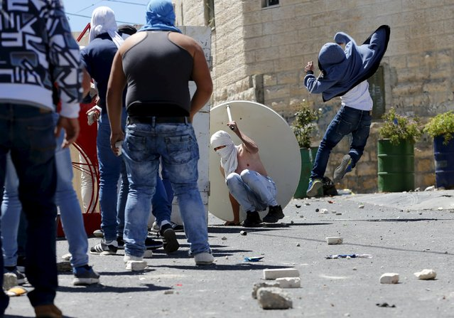 Palestinian youths throw stones towards Israeli police during clashes in the East Jerusalem neighbourhood of A-tur, after a Palestinian youth was killed by Israeli security forces April 25, 2015. (Photo by Ammar Awad/Reuters)