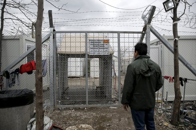 A migrant looks at the closed gate at the Greek-Macedonian border, near the village of Idomeni, at a makeshift camp for refugees and migrants near the village of Idomeni, Greece March 16, 2016. (Photo by Alkis Konstantinidis/Reuters)