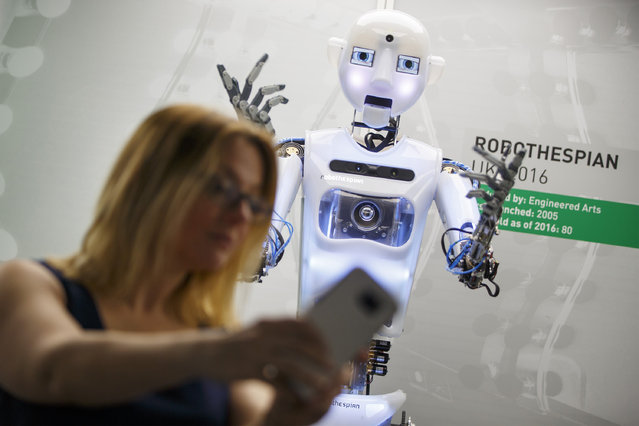 "A woman takes a selfie with ""RoboThespian"" at Robots, a major new exhibition at Science Museum in London, England on February 7, 2017. Exhibition showcases 500-year history of robots, with over 100 robots and the largest collection of humanoid robots ever displayed. (Photo by Tolga Akmen/Anadolu Agency/Getty Images)"