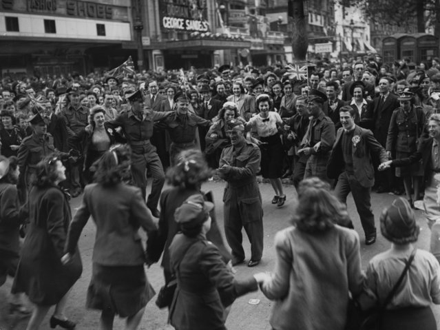 8th May 1945: Canadian troops entertain the crowds in Leicester Square while waiting for the broadcast of the King's VE Day speech. (Photo by Topical Press Agency/Getty Images)