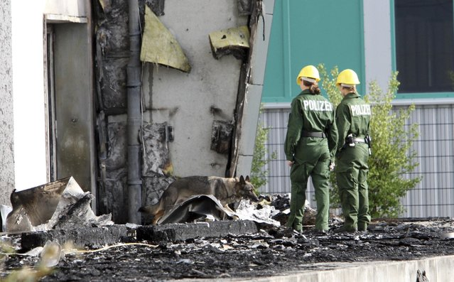 In this August 26, 2015 file picture police officers and their sniffer dog examine the ruins of a burned out gym in Nauen, Germany. A German court has convicted a far-right politician for burning down the  building intended as housing for refugees. The Potsdam court sentenced 29-year-old Maik Schneider, a member of the National Democratic Party, to eight years imprisonment for arson Thursday. February 9, 2017. (Photo by Nestor Bachmann/DPA via AP Photo)