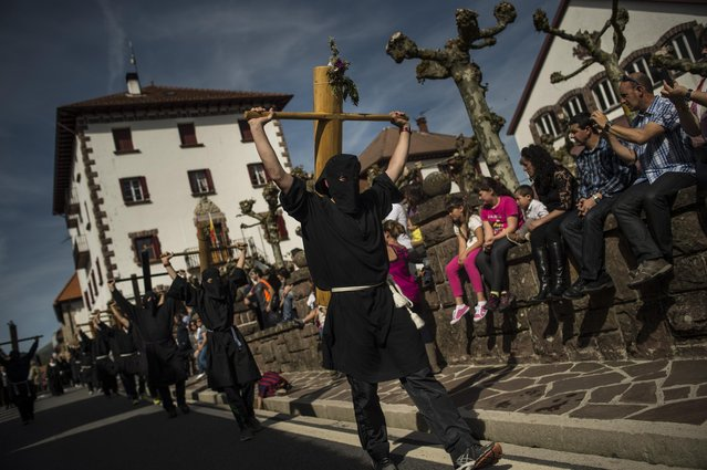 """Masked penitents holds their crosses  during spring """"Romeria Cruceros de Arce"""", while they walk past Burguete, near to Roncesvalles northern Spain Sunday, May 10, 2015. (Photo by Alvaro Barrientos/AP Photo)"""