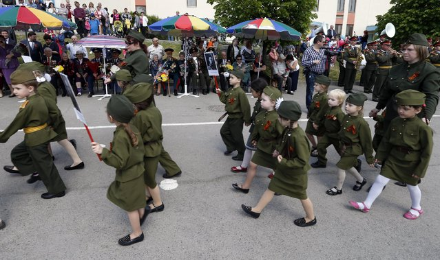 Children wearing specially made uniforms, march in front of WWII veterans,  along a street during the so-called Kid Parade in Rostov-on-Don, Russia, Thursday, May 14, 2015. (Photo by AP Photo/Stringer)