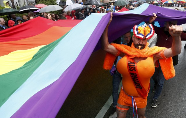 A Dutch participant blows a whistle as he holds a giant rainbow flag during the Belgian lesbian, gay, bisexual and transgender (LGBT) Pride Parade in Brussels, Belgium, May 16, 2015. (Photo by Francois Lenoir/Reuters)