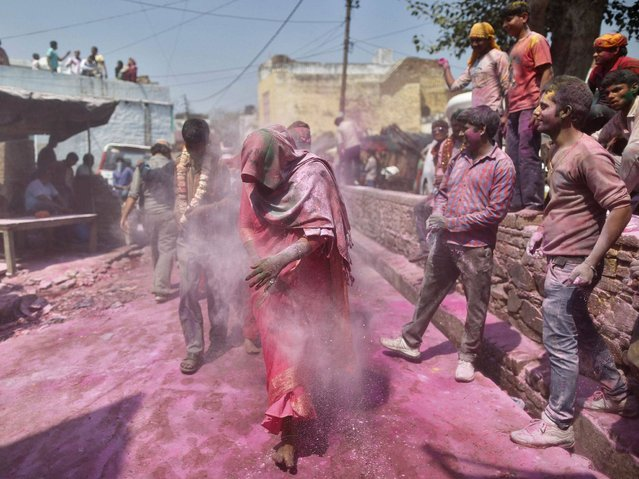"In a Holi tradition unique to Barsana and Nandgaon villages, men sing provocative songs to gain the attention of women, who then ""beat"" them with bamboo sticks called ""lathis"". (Photo by Anindito Mukherjee/Reuters)"