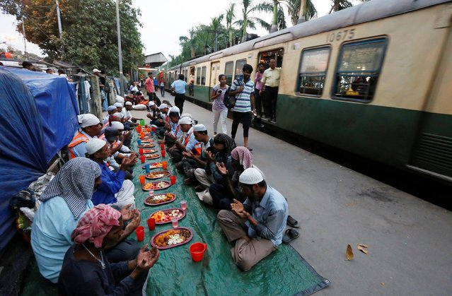 Muslim men pray as they sit before their iftar (breaking of fast) meal next to a train passing on a railway platform during the holy fasting month of Ramadan, in Kolkata, India May 13, 2019. (Photo by Rupak De Chowdhuri/Reuters)