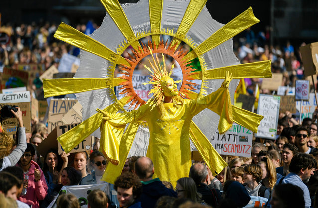 "Youth climate activists, with one of them dressed up as a sun, protest with placards as they take part in the ""Fridays for Future"" demonstration for a better climate policy in front of the cathedral of Cologne, western Germany, on May 24, 2019. The Youth climate action group calls for record mobilisation ahead of the May 26 European elections. (Photo by  Ina Fassbender/AFP Photo)"